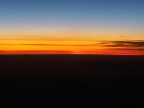 A horizon just before sunrise, the land dark, the sky shading from orange through gold to a deepening blue. A few long, narrow, dark clouds parallel the horizon, accentuating the coloured bands of the sky.