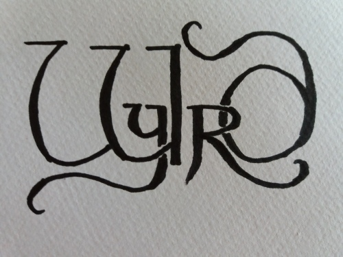 The word wyrd, letters shaped in an old-fashioned style, in black on textured white paper