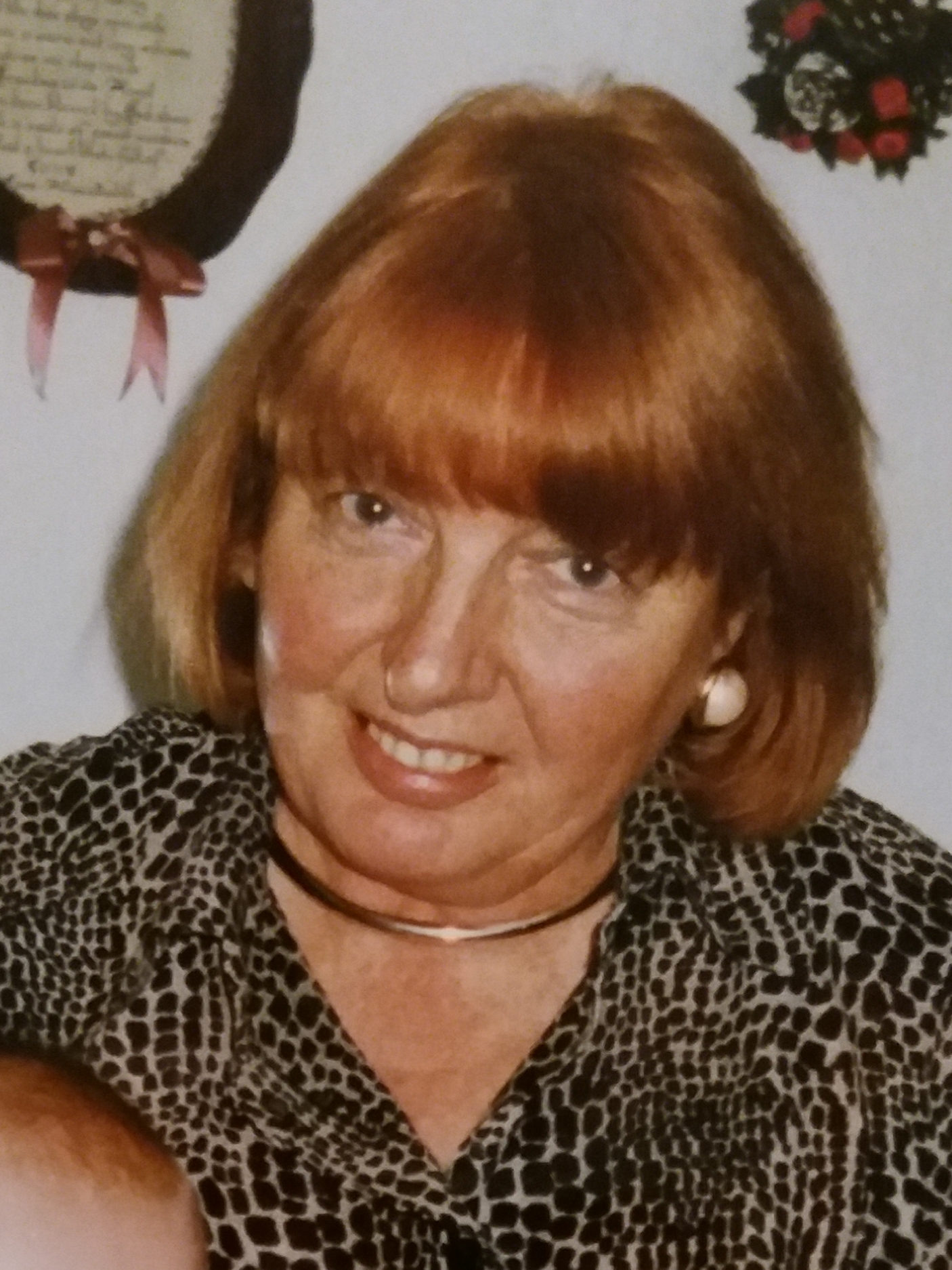 A photo of a middle-aged woman with red hair and a warm smile