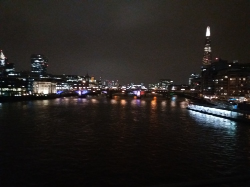 A night-time view down the Thames from the Millennium Bridge towards Tower Bridge, visible in the distance. The city lights shine and are reflected from the water