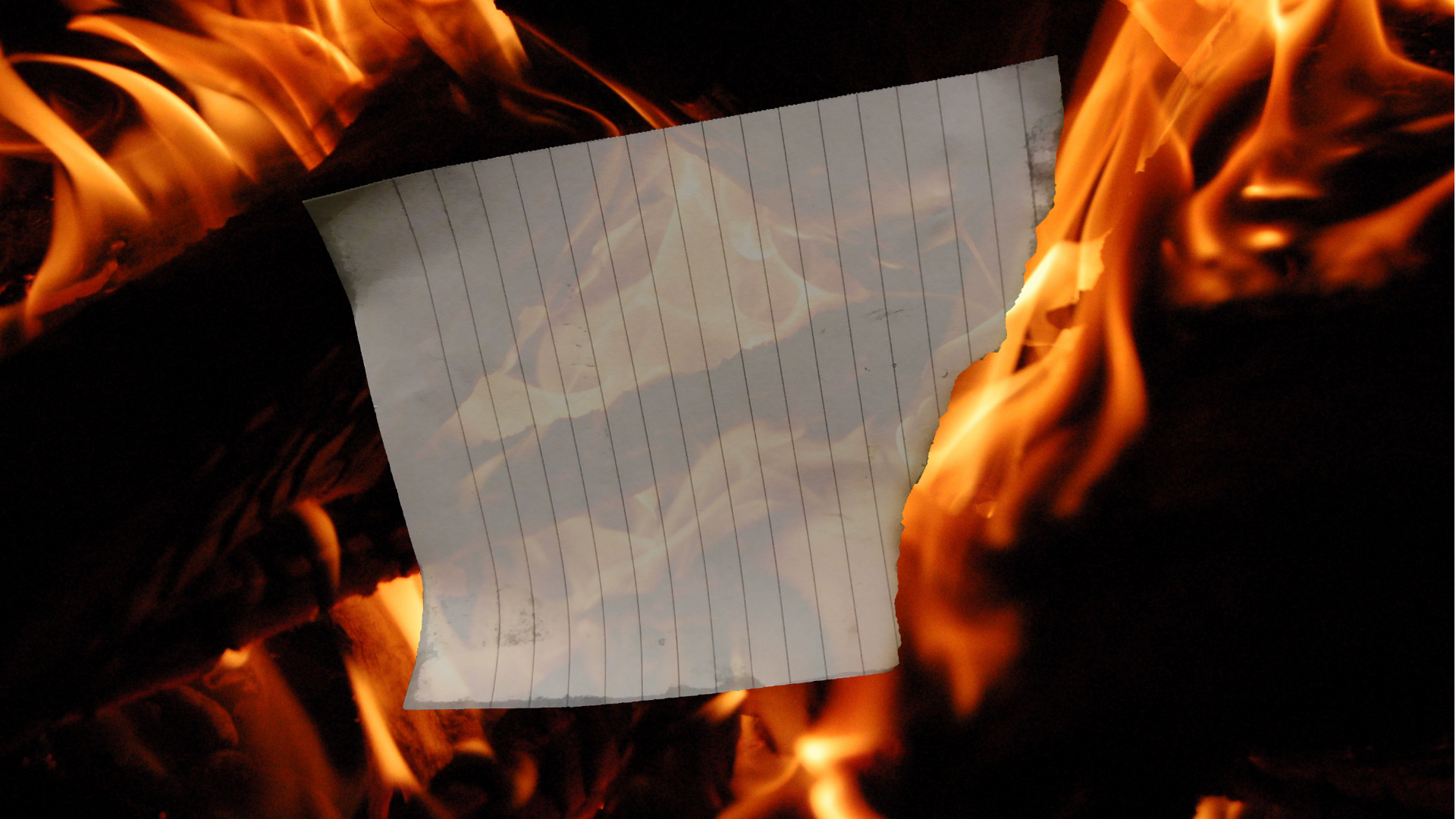 A torn page in front of a burning fire