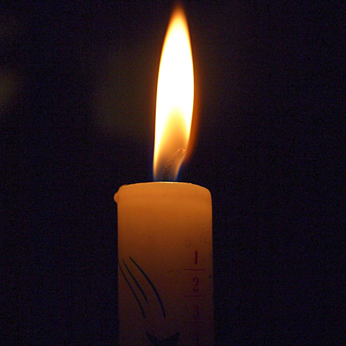 Close-up of a burning candle flame against a black background