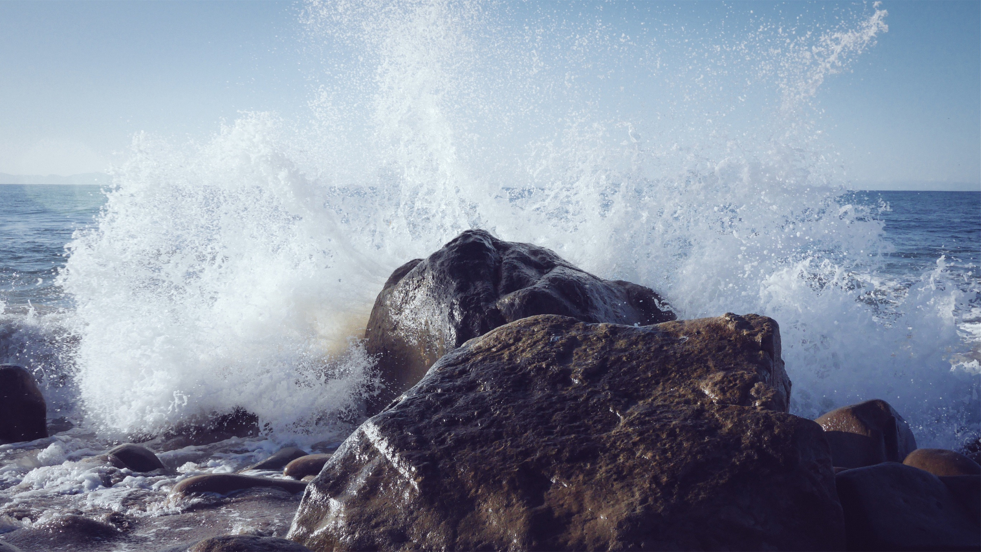 Waves crash into a solid rock, spraying high