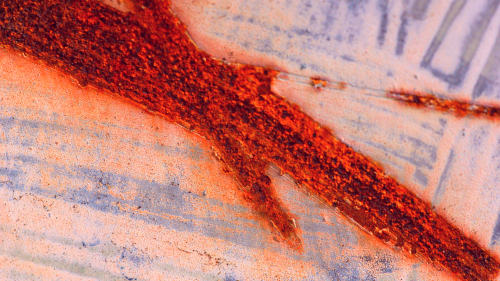 Close-up of a rusted scratch on a steel plate, looking like torn skin