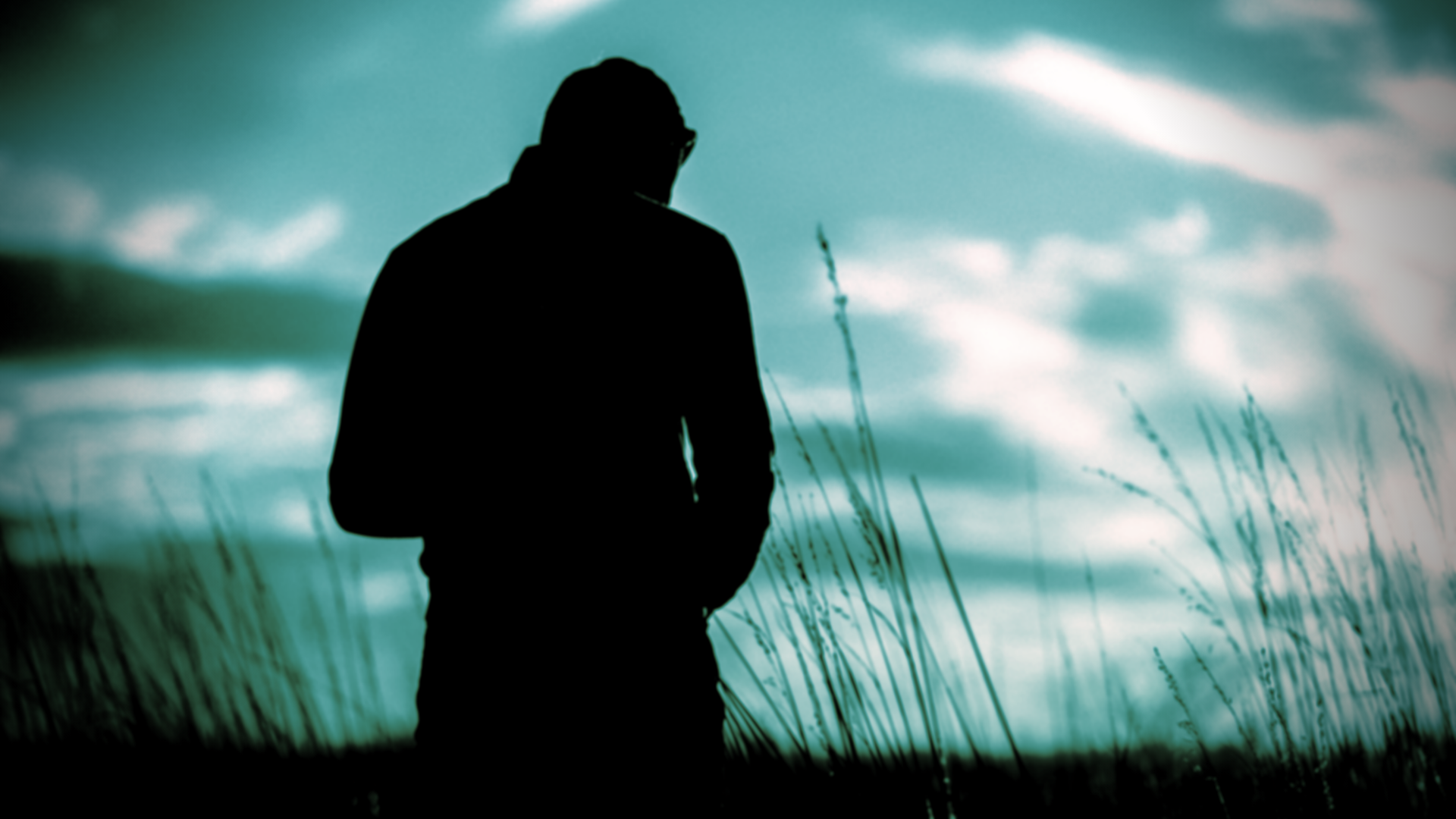 A man, head bowed and facing away, silhouetted against a dramatic sky.