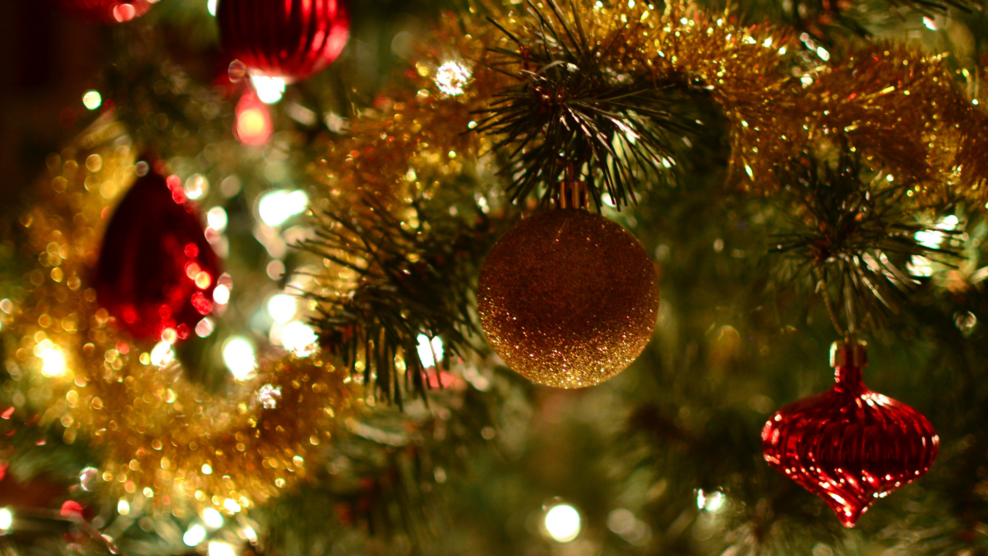 Shiny, glittering red and gold baubles and gold tinsel adorn a green Christmas tree