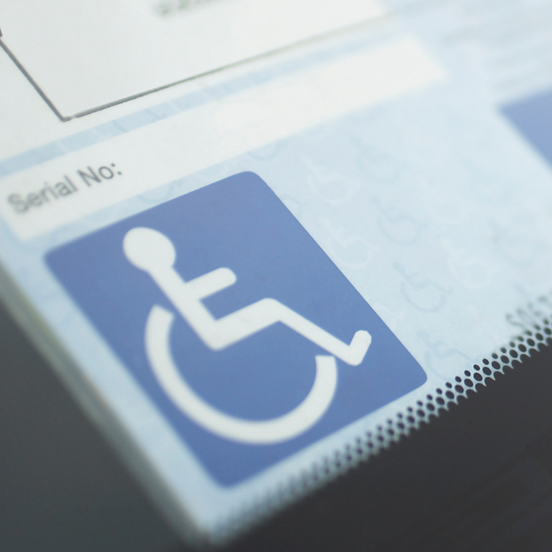 A close-up of a UK disability Blue Badge showing the white on blue disabled symbol on its lower left corner