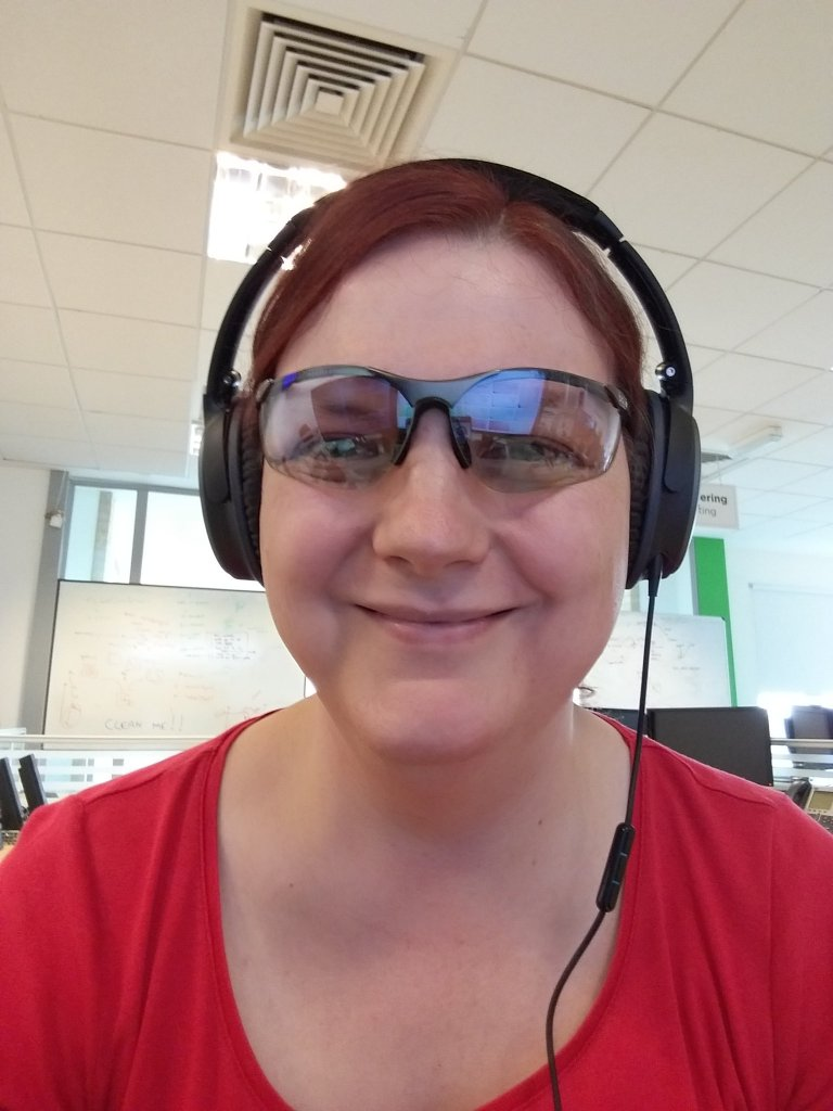 Photograph of the author at work, smiling, and wearing tinted eye glasses and headphones